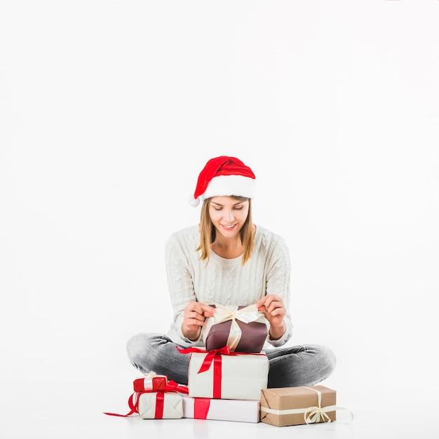 Frau, die geschenke auf fußboden betrachtet