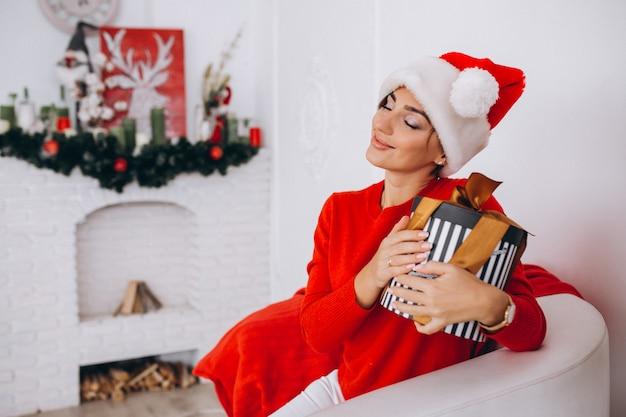 Frau, die geschenke auf weihnachten auspackt