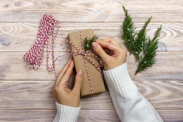 Frau, die geschenke für weihnachten einwickelt. hände der frau weihnachtsgeschenkbox verzierend