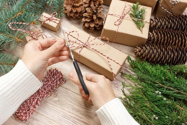 Frau, die geschenke für weihnachten einwickelt.