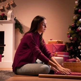 Frau, die geschenke für weihnachtstag einwickelt