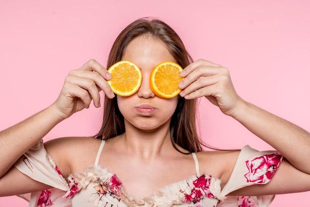 Frau, die geschnittene orange zu den augen setzt und spaß hat