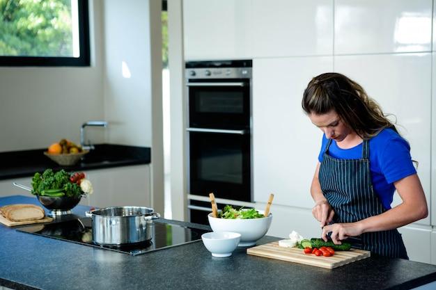 Frau, die geschnittenes gemüse für abendessen in der küche vorbereitet