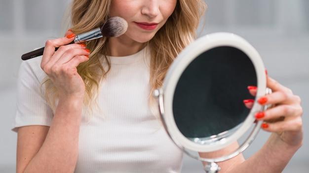 Frau, die gesicht beim spiegeln pulverisiert