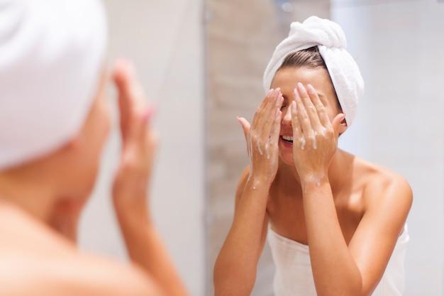 Frau, die gesicht im badezimmer wäscht