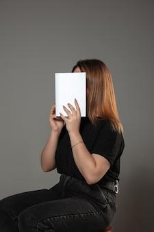 Frau, die gesicht mit buch bedeckt, während sie an grauer wand liest. feiern, bildung, kunst, neues charakterkonzept genießen.