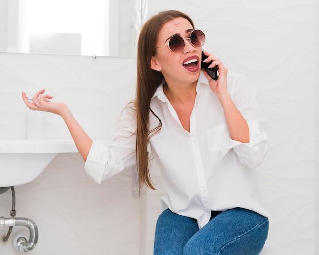 Frau, die gesichter macht und am telefon spricht