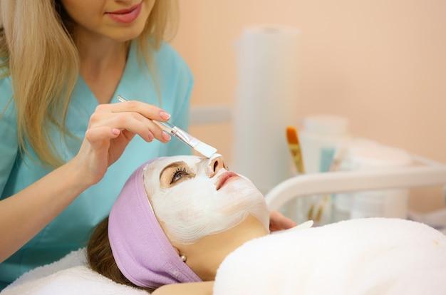 Frau, die gesichtsbehandlung von einem cosmetologist in einem badekurort empfängt.