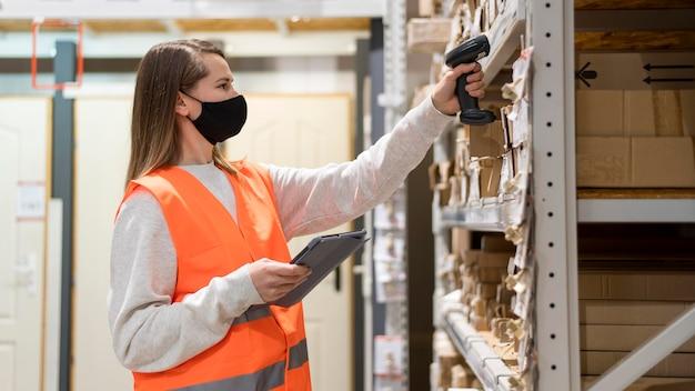 Frau, die gesichtsmaske am arbeitsplatz trägt