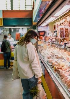 Frau, die gesichtsmaske am markt trägt