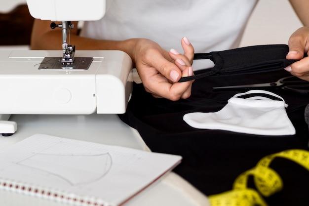 Frau, die gesichtsmaske aus textil näht
