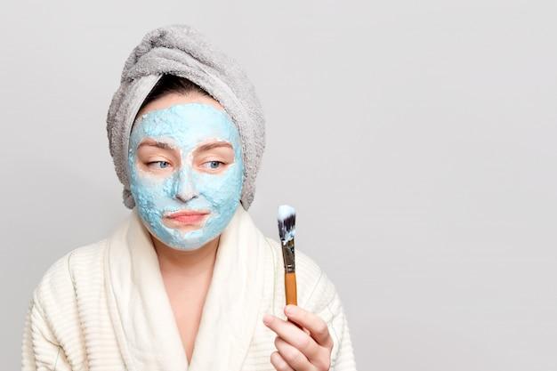 Frau, die gesichtsmaske des tons im spa-salon oder zu hause, hautpflegethema anwendet. gesichtsmaske, spa-schönheitsbehandlung mit kopierraum