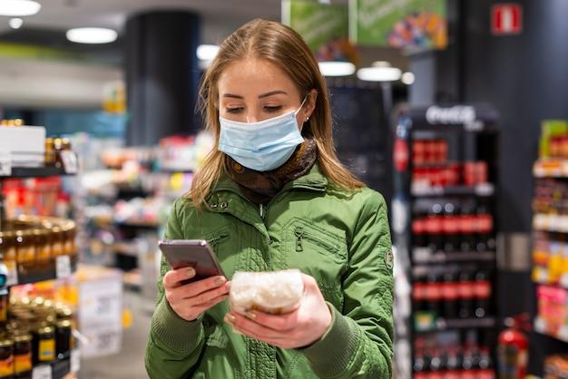 Frau, die gesichtsmaske im geschäft trägt und ihr telefon betrachtet