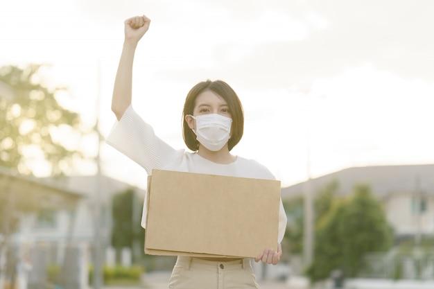 Frau, die gesichtsmaske trägt, die ein leeres plakat hält, um den text auf protest zu setzen.
