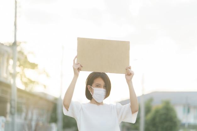 Frau, die gesichtsmaske trägt, die ein leeres plakat hält