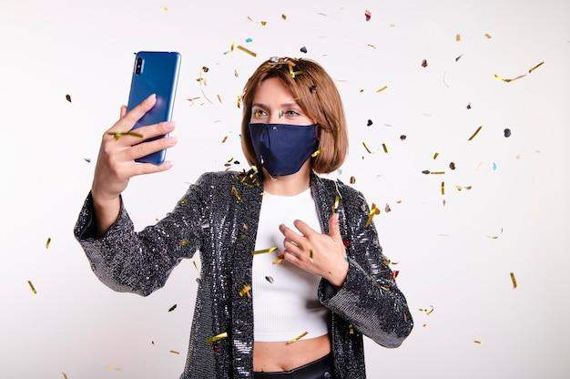 Frau, die gesichtsmaske trägt, die ein selfie nimmt