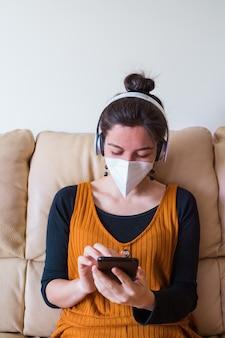 Frau, die gesichtsmaske trägt, die einen freund zu hause anruft. menschen mit coronavirus-krankheit auf der couch zu hause infiziert. zu hause bleiben. pandemieviruskrankheit covid 19.