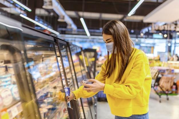 Frau, die gesichtsmaske trägt, die im supermarkt kauft.