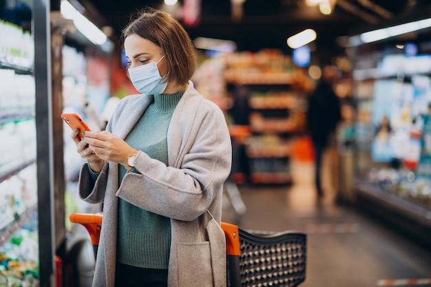 Frau, die gesichtsmaske trägt und im lebensmittelgeschäft einkauft