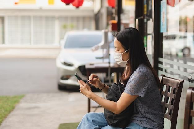 Frau, die gesichtsmaske unter verwendung des mobilen wartens auf herausnehmen essen außerhalb des restaurants trägt.