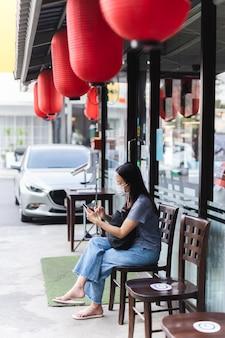 Frau, die gesichtsmaske unter verwendung des mobilen wartens auf tisch außerhalb restaurant trägt.