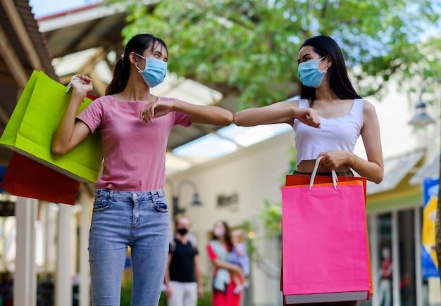 Frau, die gesichtsmaskeneinkauf im kaufhaus trägt