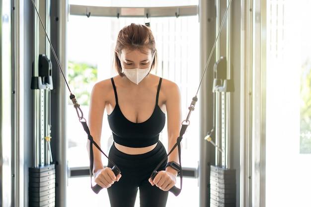 Frau, die gesichtsmaskenübung brusttraining auf bankdrücken kabelmaschine crossover im fitnessstudio trägt. während des corona-virus pandermic.