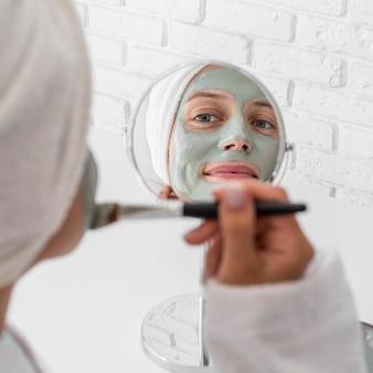 Frau, die gesichtsmittel im spiegel anwendet