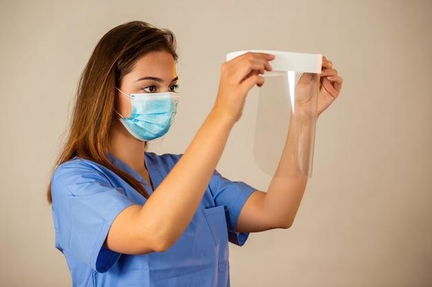 Frau, die gesichtsschutz in einem krankenhaus von der seitenansicht anbringt