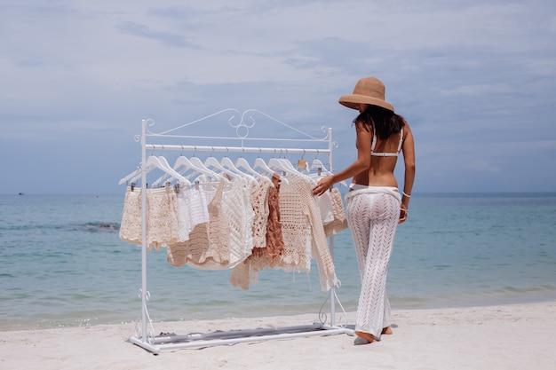 Frau, die gestrickte kleidung von kleiderbügeln am strand wählt