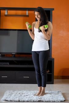 Frau, die gewichte glücklich zu hause in ihrem wohnzimmer trägt sportbekleidung tut
