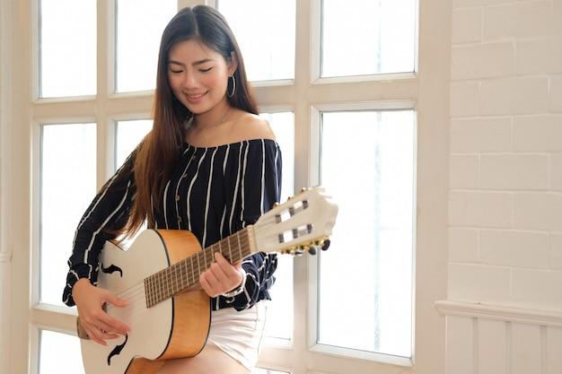 Frau, die gitarre drinnen spielt