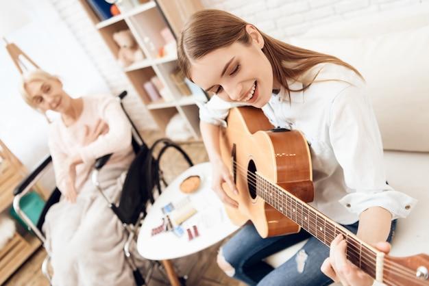Frau, die gitarre für alte dame im rollstuhl spielt.