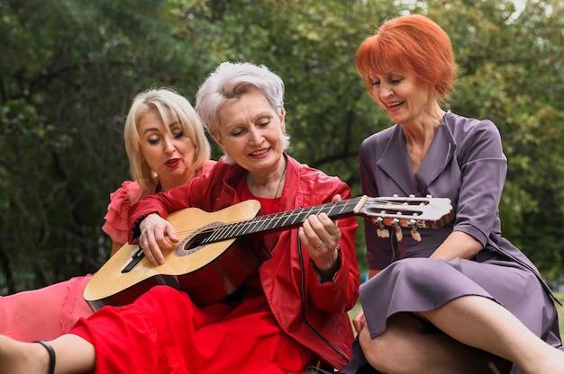 Frau, die gitarre für freunde spielt