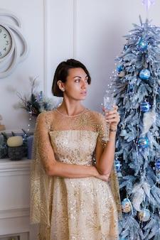Frau, die glänzendes goldenes abendweihnachtskleid hält, das glas champagner durch blauen jahrbaum zu hause hält