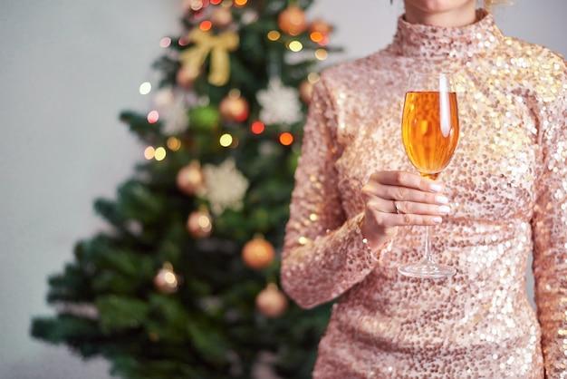 Frau, die glas champagner mit weihnachtsbaum hält