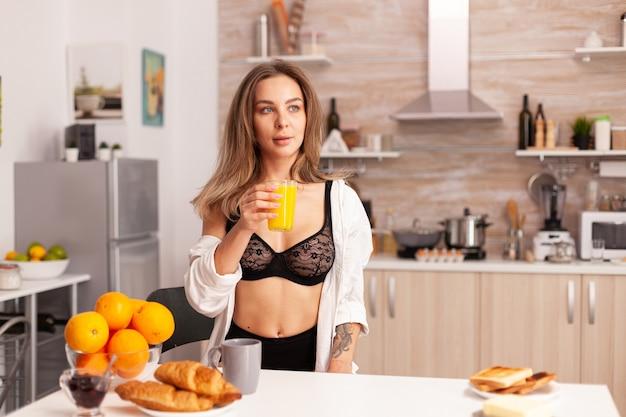 Frau, die glas mit frischem orangensaft während des frühstücks hält, das sexy schwarze wäsche trägt. junge sexy verführerische blutdame mit tattoos trinkt gesunden, natürlichen hausgemachten orangensaft, erfrischenden sunda refreshing