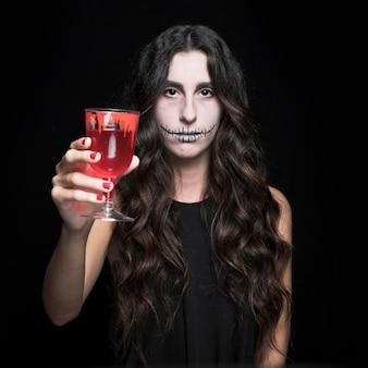 Frau, die glas mit roter flüssigkeit hochlädt