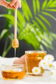 Frau, die glas mit tee und honigschöpflöffel hält