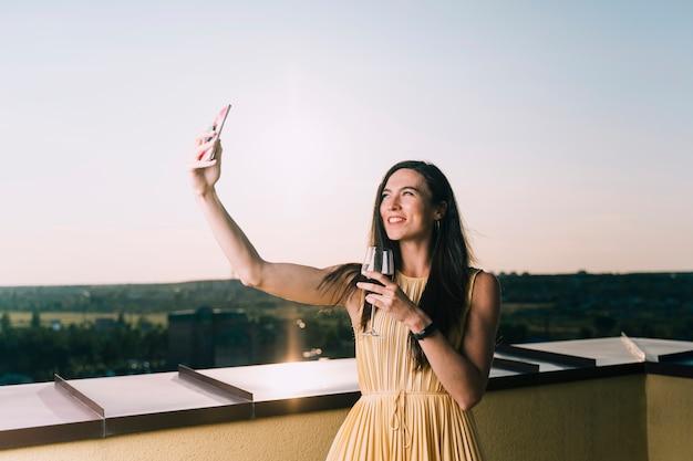 Frau, die glas wein hält und selfie auf der dachspitze nimmt