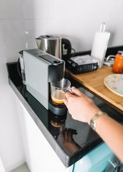 Frau, die glasbecher unter der kaffeemaschine hält