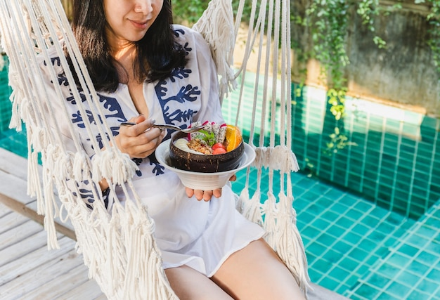 Frau, die glattes frühstück sitzt, das auf hängematte durch schwimmbad sitzt.