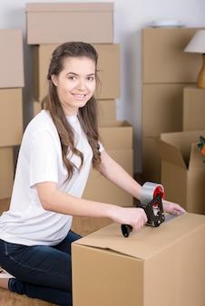 Frau, die glücklich bewegliche kästen im wohnzimmer auspackt.