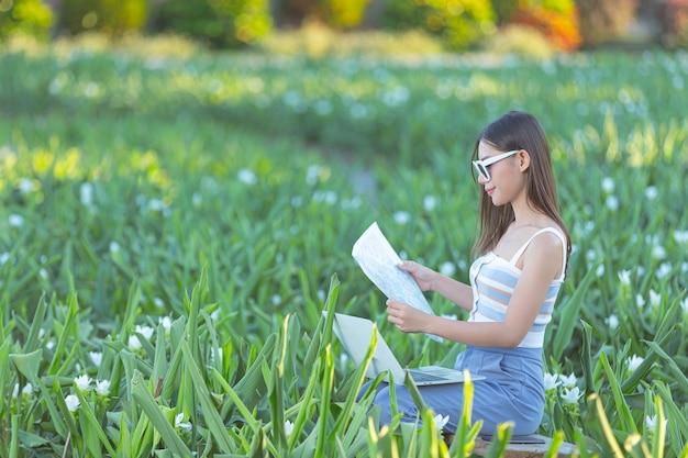 Frau, die glücklich eine touristische karte im blumengarten hält