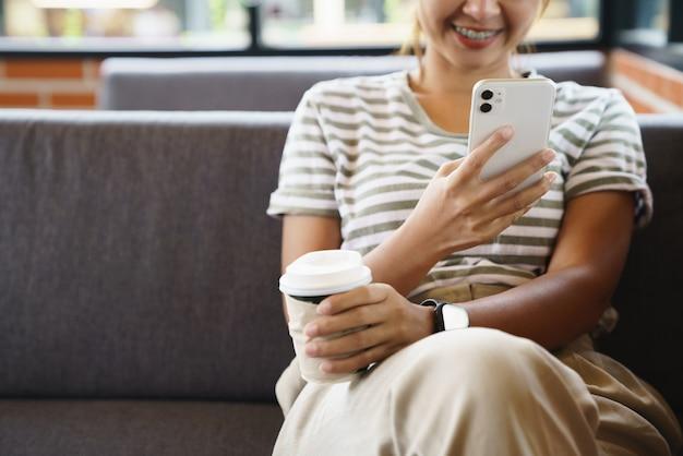 Frau, die glücklich ist, telefon im kaffeehaus zu verwenden