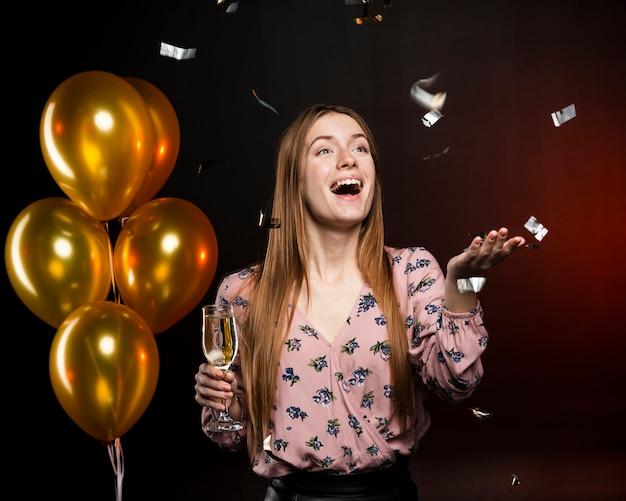 Frau, die glücklich ist und ein glas mit goldenen ballonen hält