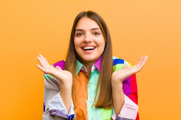 Frau, die glücklich und aufgeregt aussieht, schockiert über eine unerwartete überraschung, beide hände offen neben dem gesicht