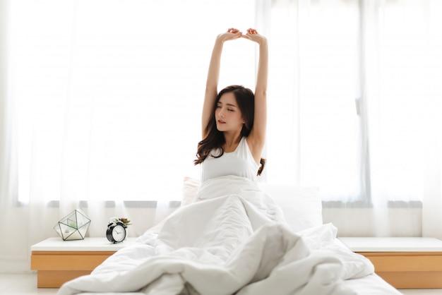 Frau, die glücklich und entspannt streckt, nachdem sie morgens zu hause aufwacht