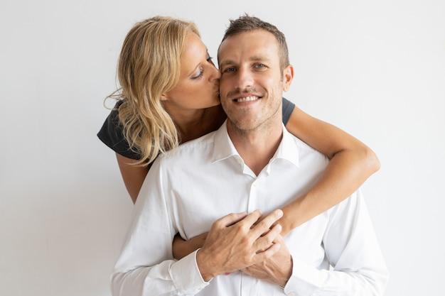 Frau, die glücklichen ehemann auf backe küsst