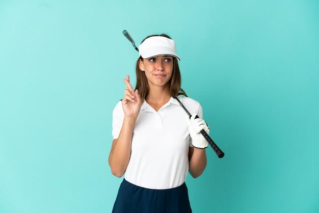 Frau, die golf spielt, isoliert mit gekreuzten fingern und wünscht das beste